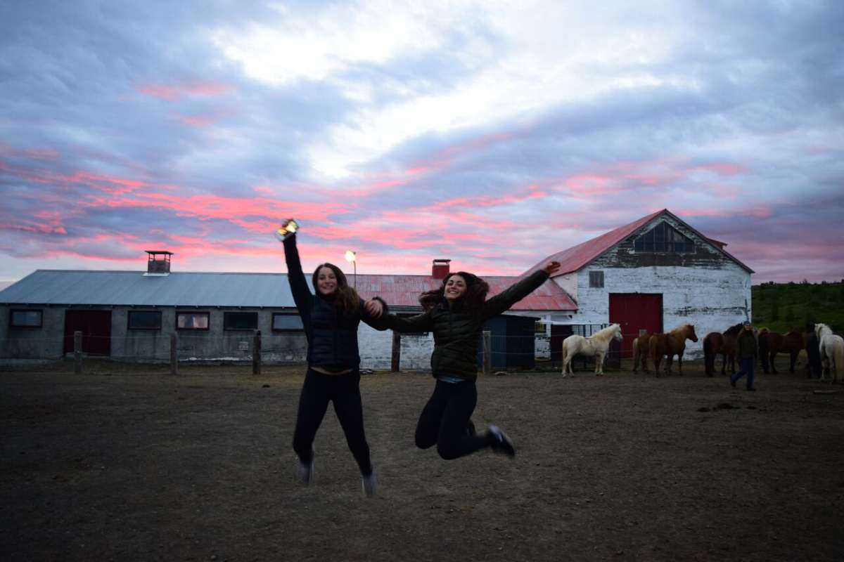 Happy teen travelers at Icelandic horse farm during summer travel adventure trip