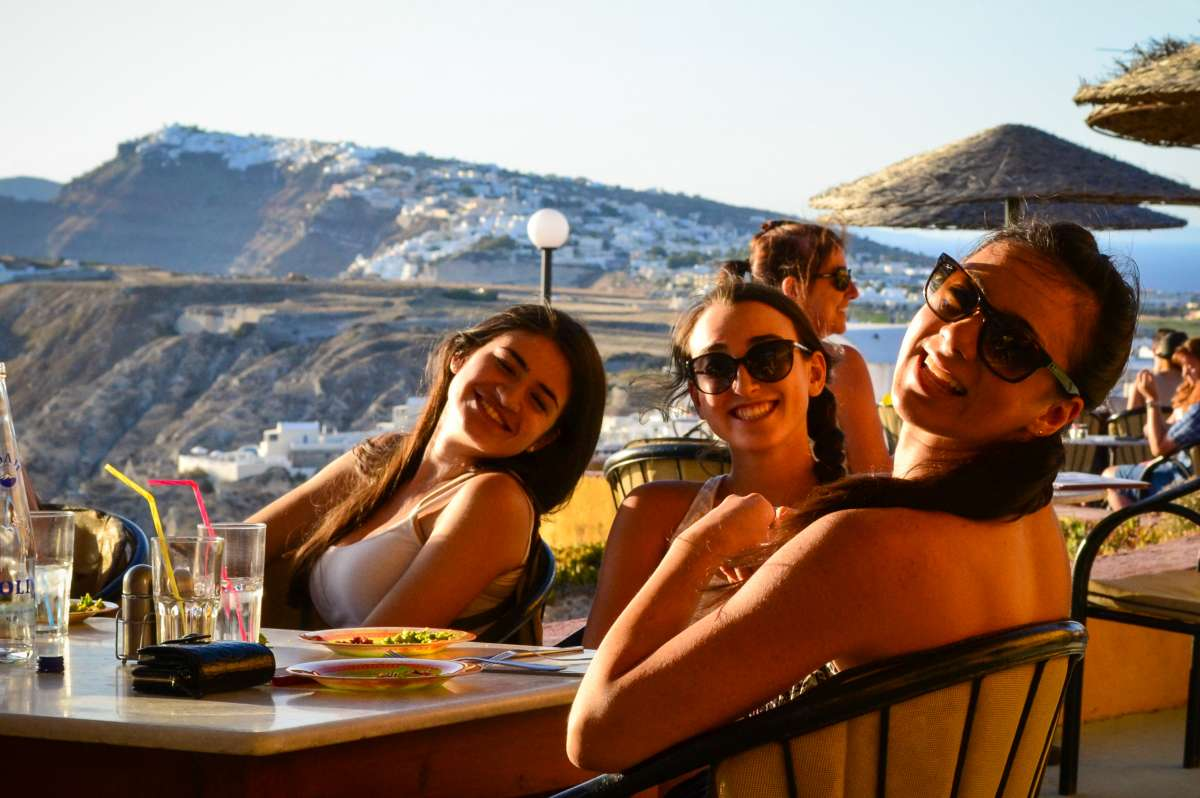 High school students basque in the sunset on Santorini on their summer teen tour to Greece.