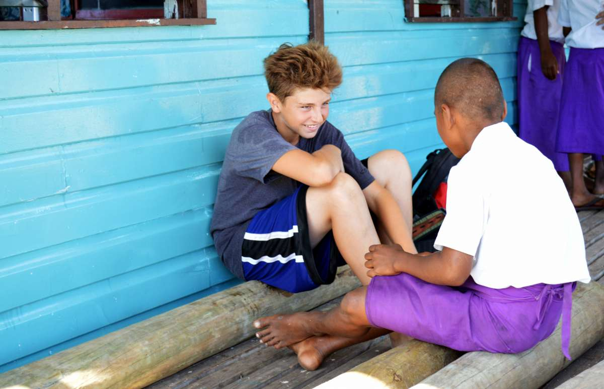 Teenage traveler talking with local Fijian boy during summer youth program in Fiji