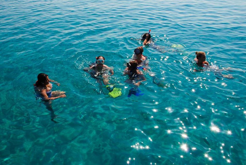 Teenage travelers swim in Mediterranean Sea during summer youth travel program in Greece