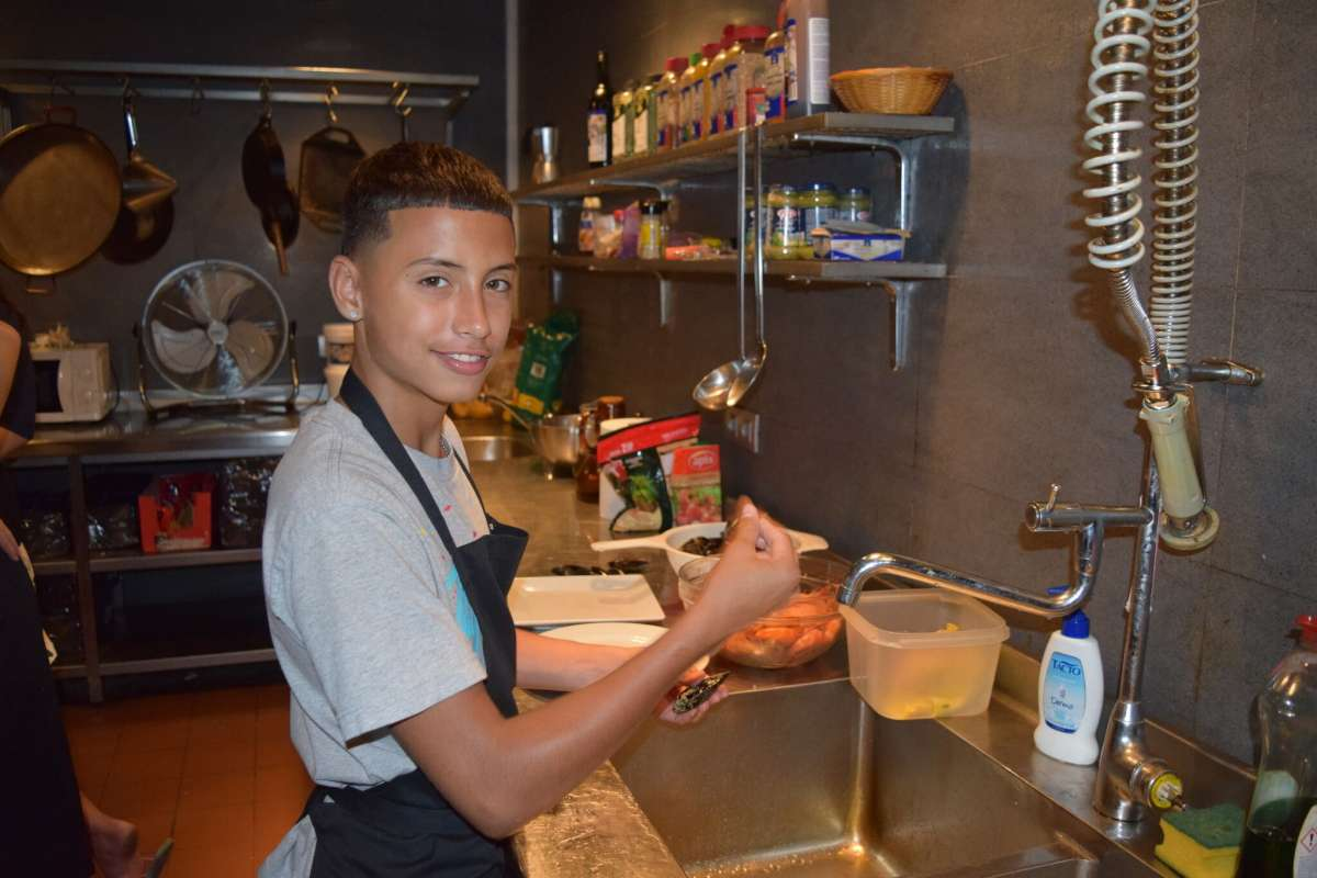 Teen traveler makes paella in cooking class on Barcelona youth travel tour