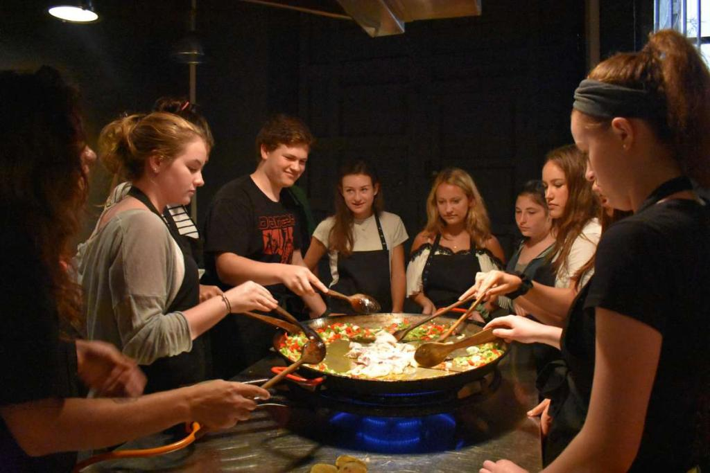 Teenage travelers make paella at cooking class in Barcelona during summer Spanish language immersion program
