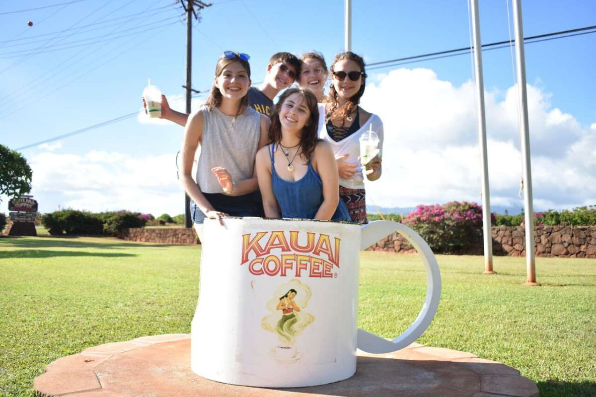 Teens pose for a photo with Kauai coffee on adventure and service program in Hawaii.