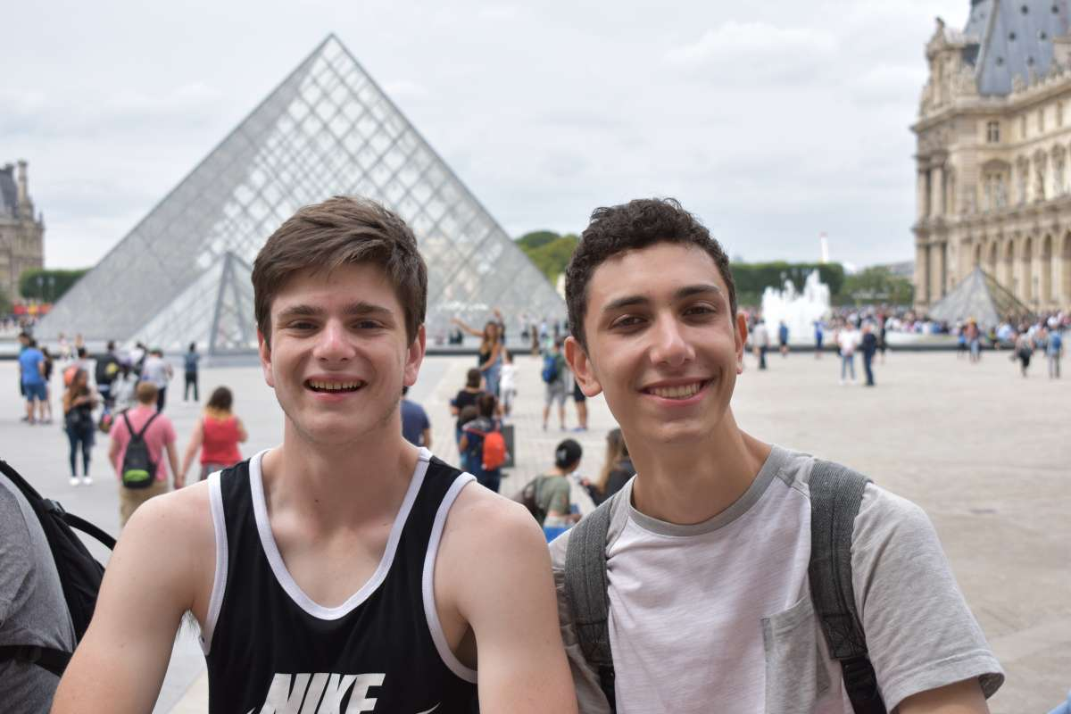 Teenage travelers at Louvre Museum in Paris during summer youth travel trip