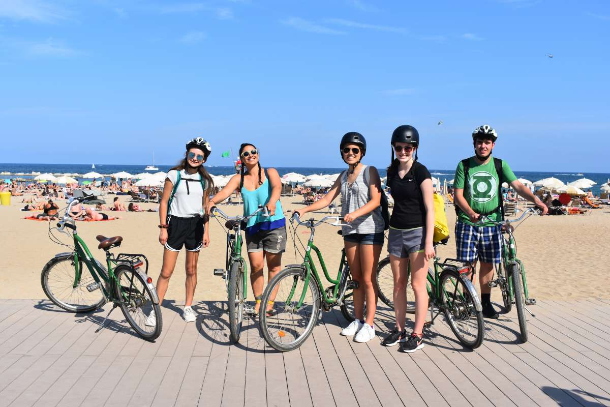 Teenage travelers biking on Barceloneta boardwalk in Barcelona during summer youth travel program