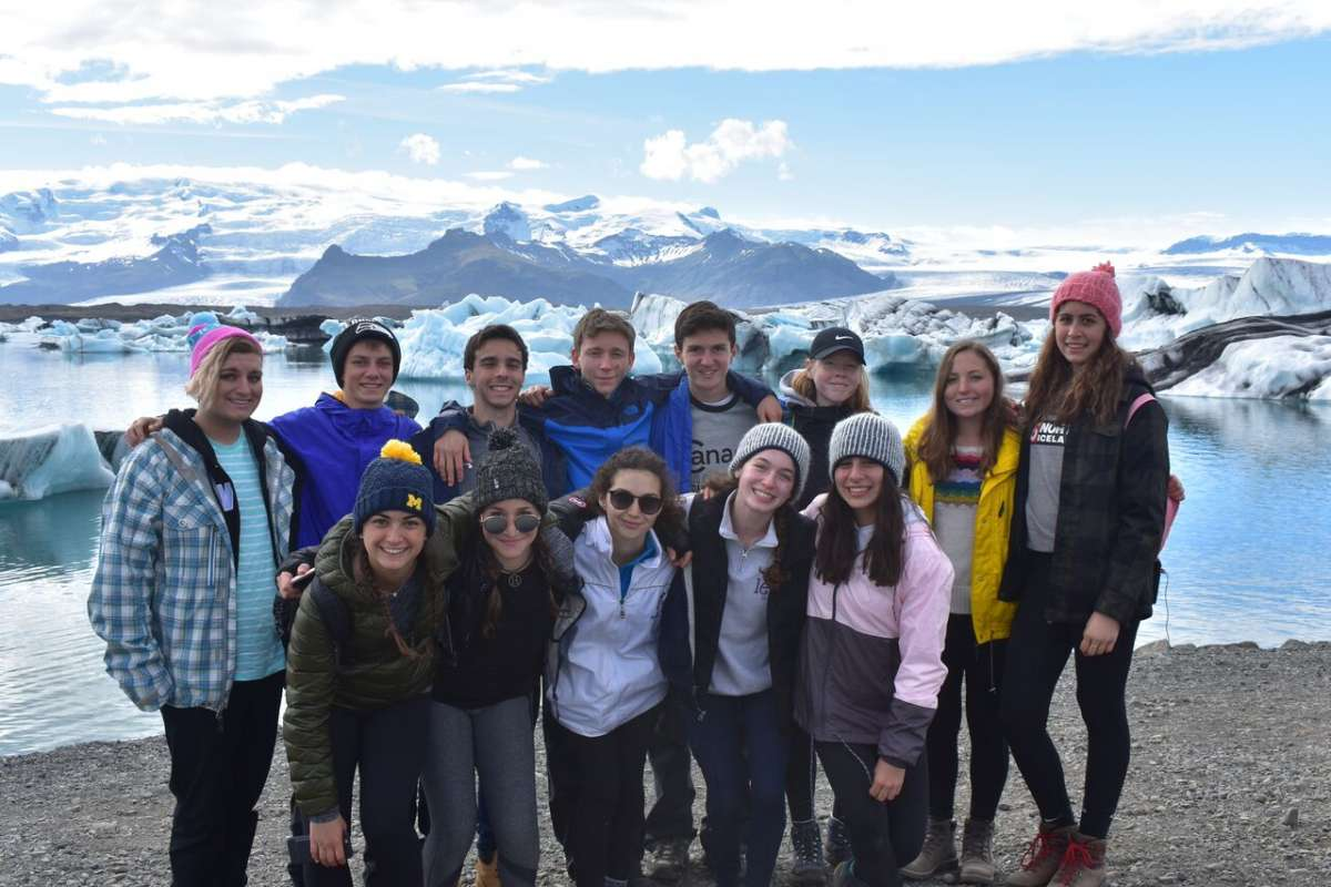 Teen travelers at Iceland glacier lagoon during summer travel adventure trip