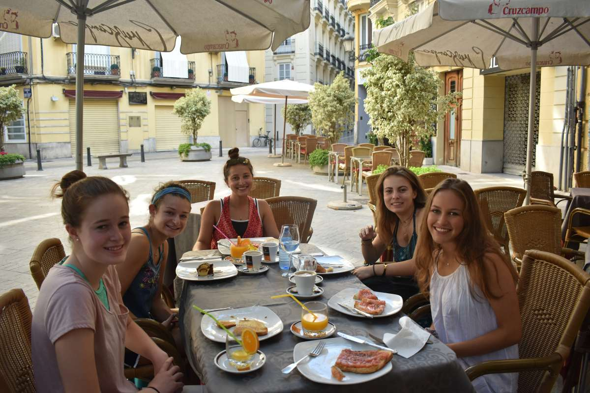 Teenage travelers eating breakfast brunch in Valencia during summer Spanish language immersion program