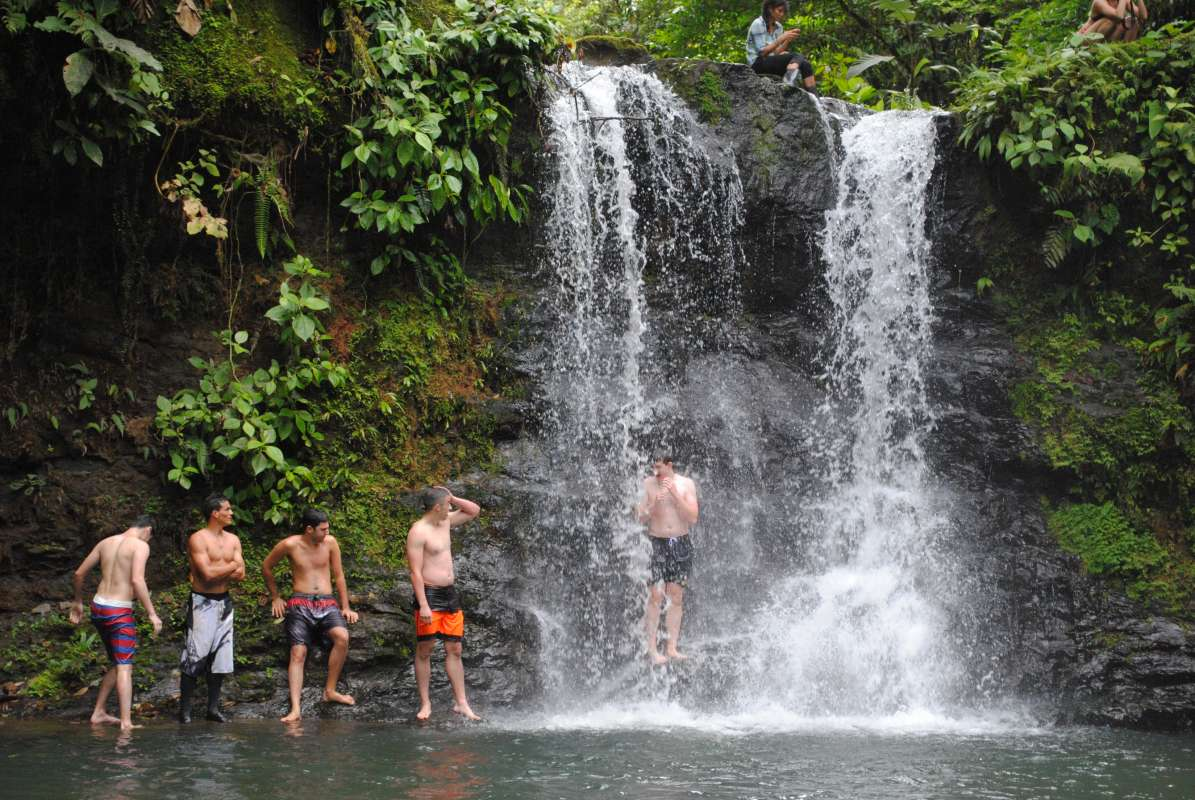 Group of teen boys explores a waterfall in Costa Rica on their summer adventure tour.