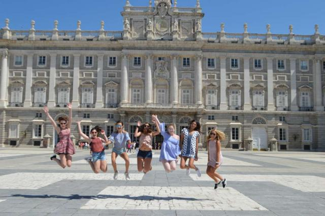 Happy teenage travelers jump in front of Madrid royal palace on summer Spanish language immersion program