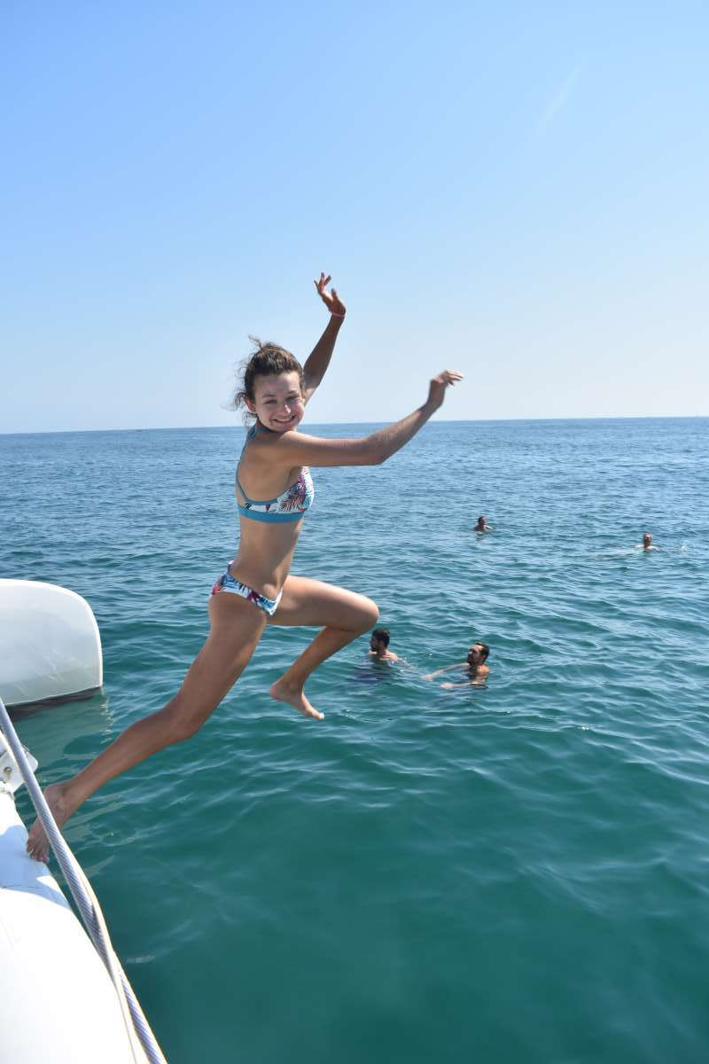 Teenage traveler jumping into Mediterranean Sea in Valencia during summer Spanish language immersion program