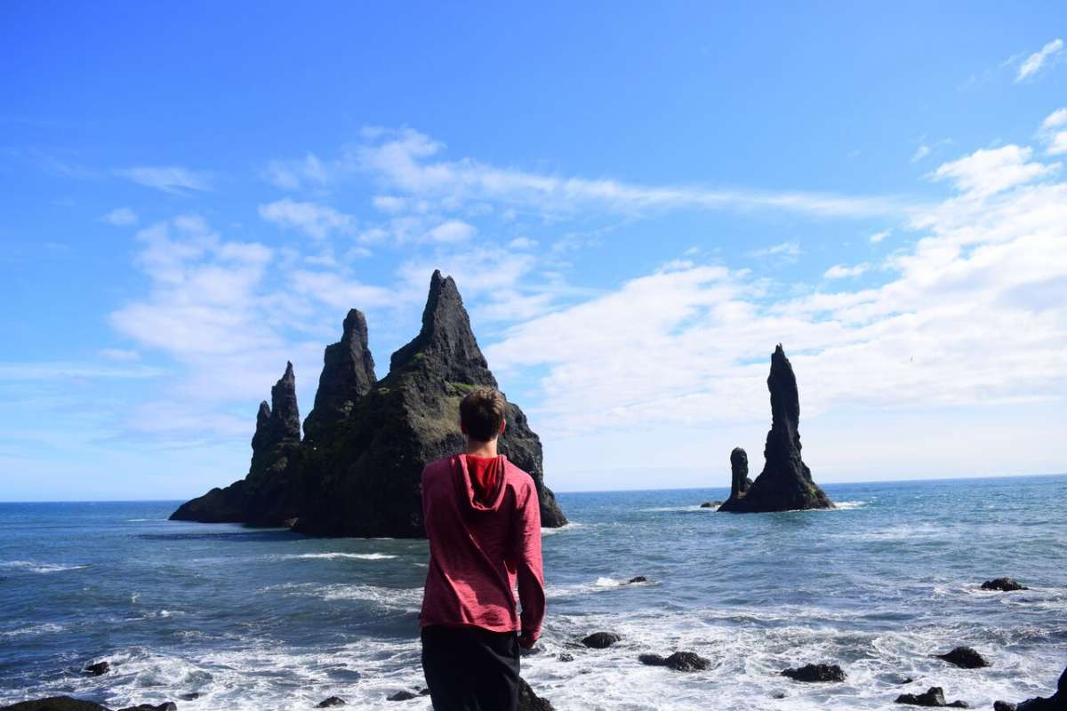 Teenage traveler with Iceland seascape on summer adventure travel program