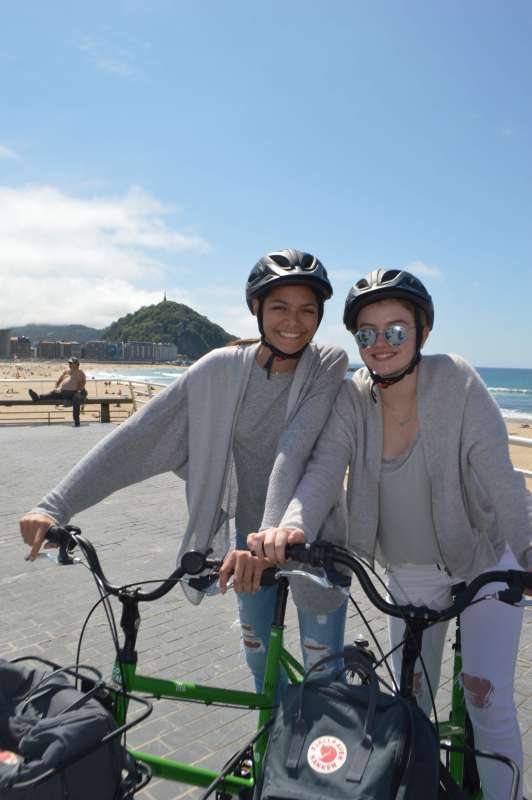 Teenage travelers biking in San Sebastian during summer Spanish language immersion program
