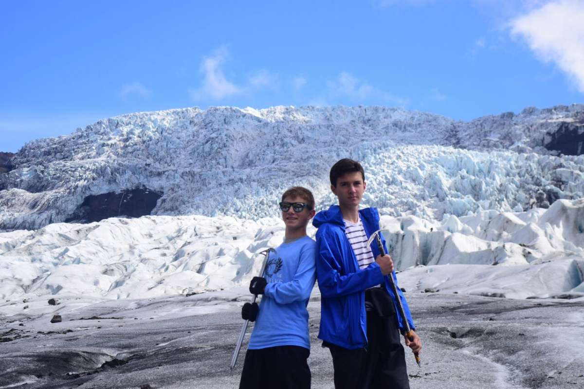Teen travelers climbing ice glacier in Iceland on summer youth adventure travel program