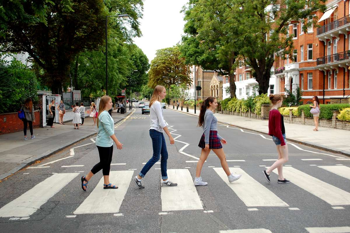 Teenage travelers cross Beatles Abbey Road in London on summer youth travel program