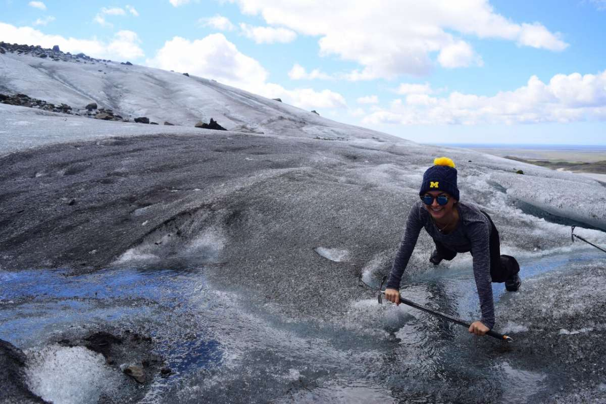 Teen traveler climbing ice glacier in Iceland on summer youth adventure travel program