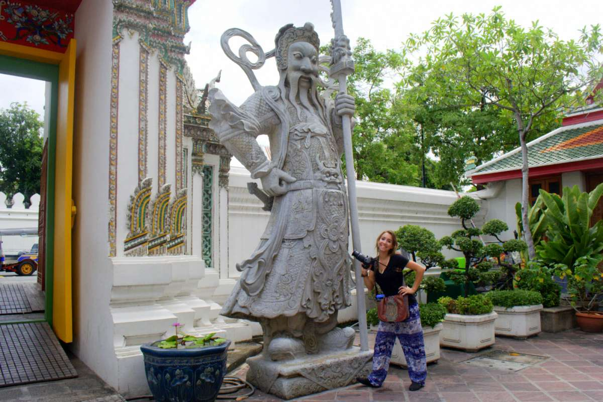 Teenage traveler admires local art statue during summer youth travel program in Southeast Asia
