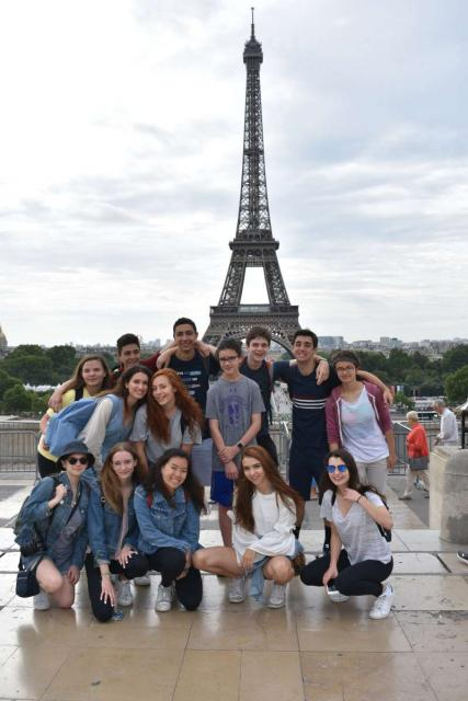 Teen travelers at Eiffel Tower in France during summer travel program
