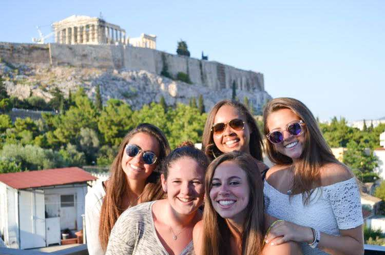 Teen travelers pose with Acropolis in Athens during summer youth travel program in Greece