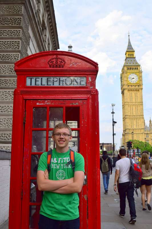 Teenage traveler with red phone box and Big Ben in London on summer youth travel program