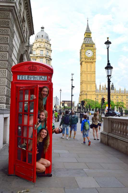 Teenage travelers in red phone box by Big Ben in London on summer youth travel program