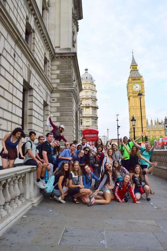 Group of teenage travelers with Big Ben and red phone box during summer teen travel program in London England
