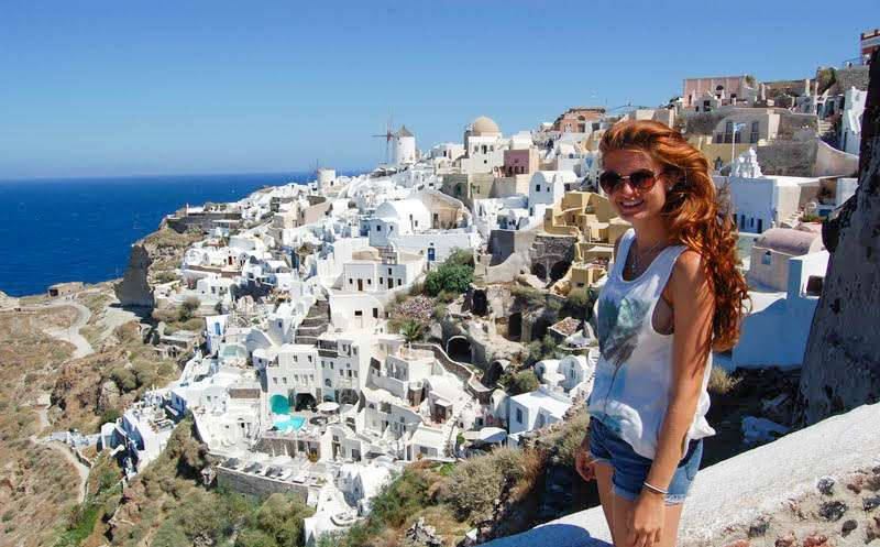 Teen traveler visits whitewashed village of Santorini during summer youth travel program in Greece