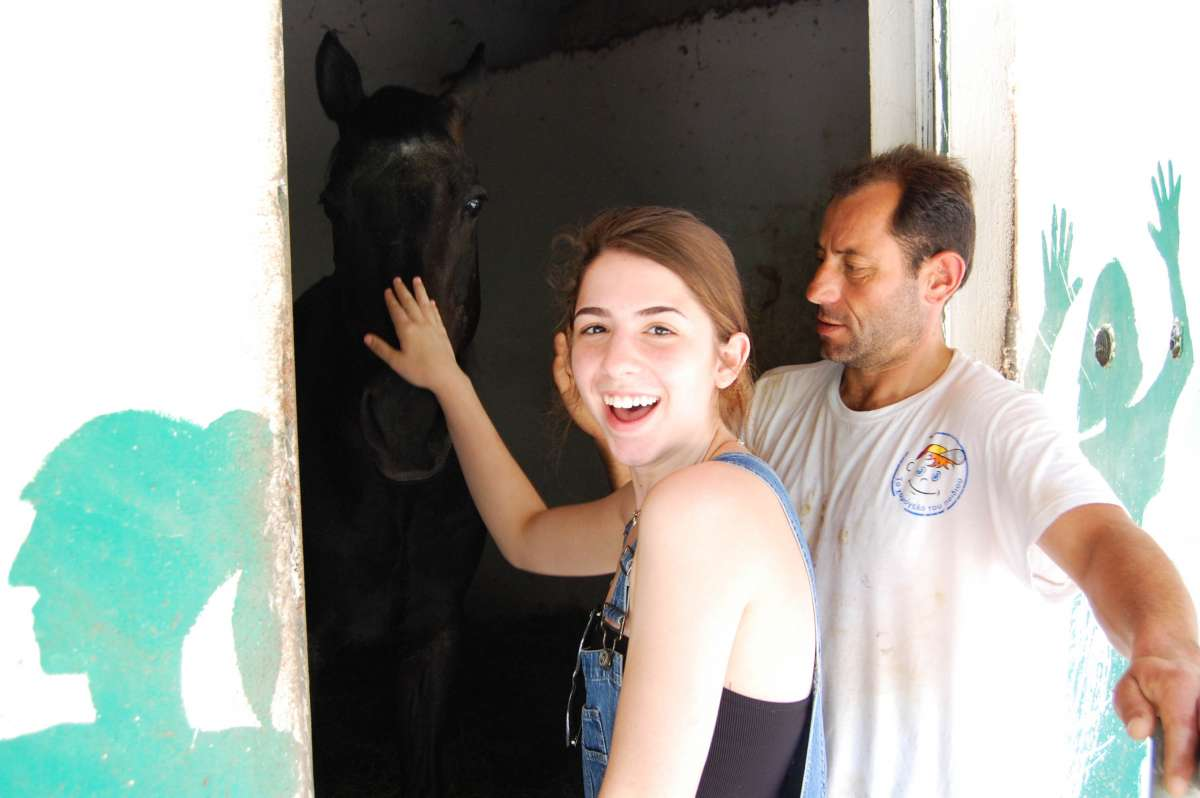 Happy teenage traveler pets horse during summer youth travel program in Greece