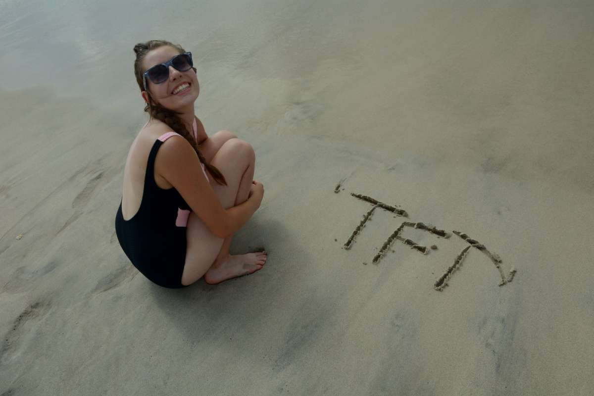 Teen writes in the sand on summer travel program in Costa Rica.