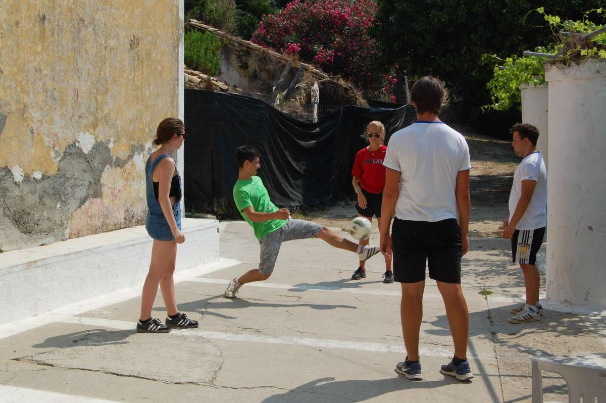 Teenage travelers play soccer with local school children during summer youth travel program in Greece