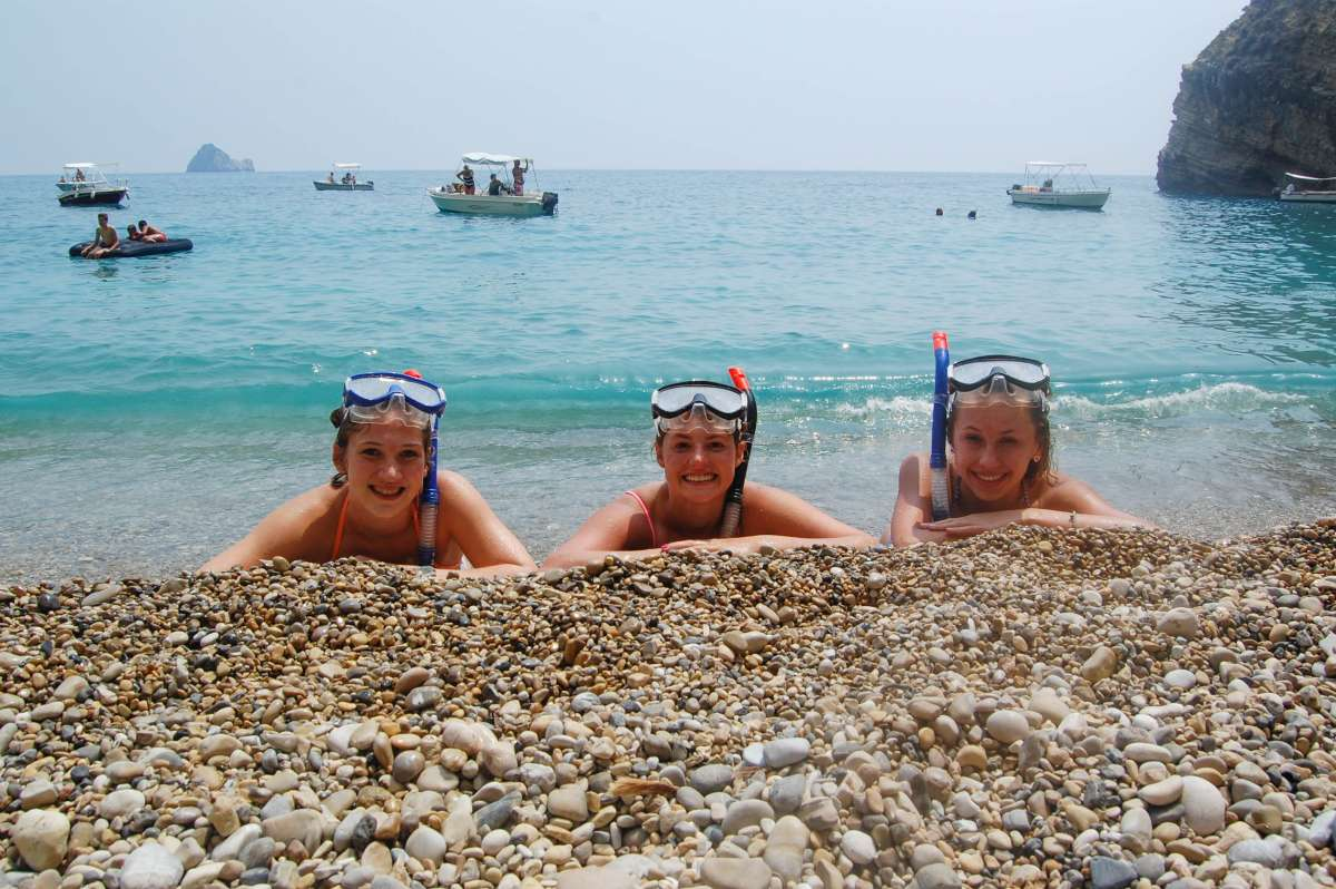 Teenage travelers snorkel and swim in Mediterranean sea during summer youth travel program in Greece
