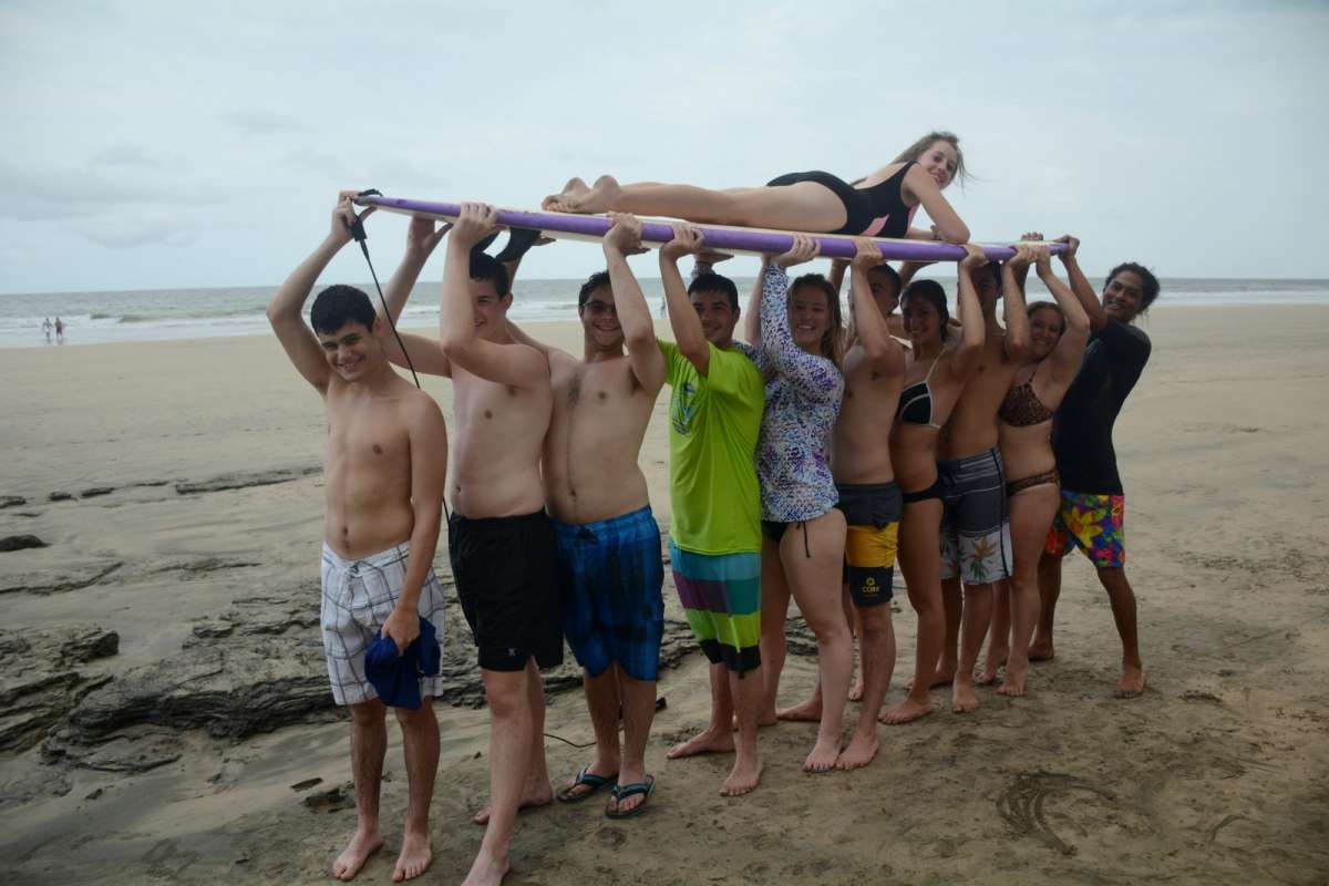 Group of teens carries friend on surfboard on summer travel program in Costa Rica.