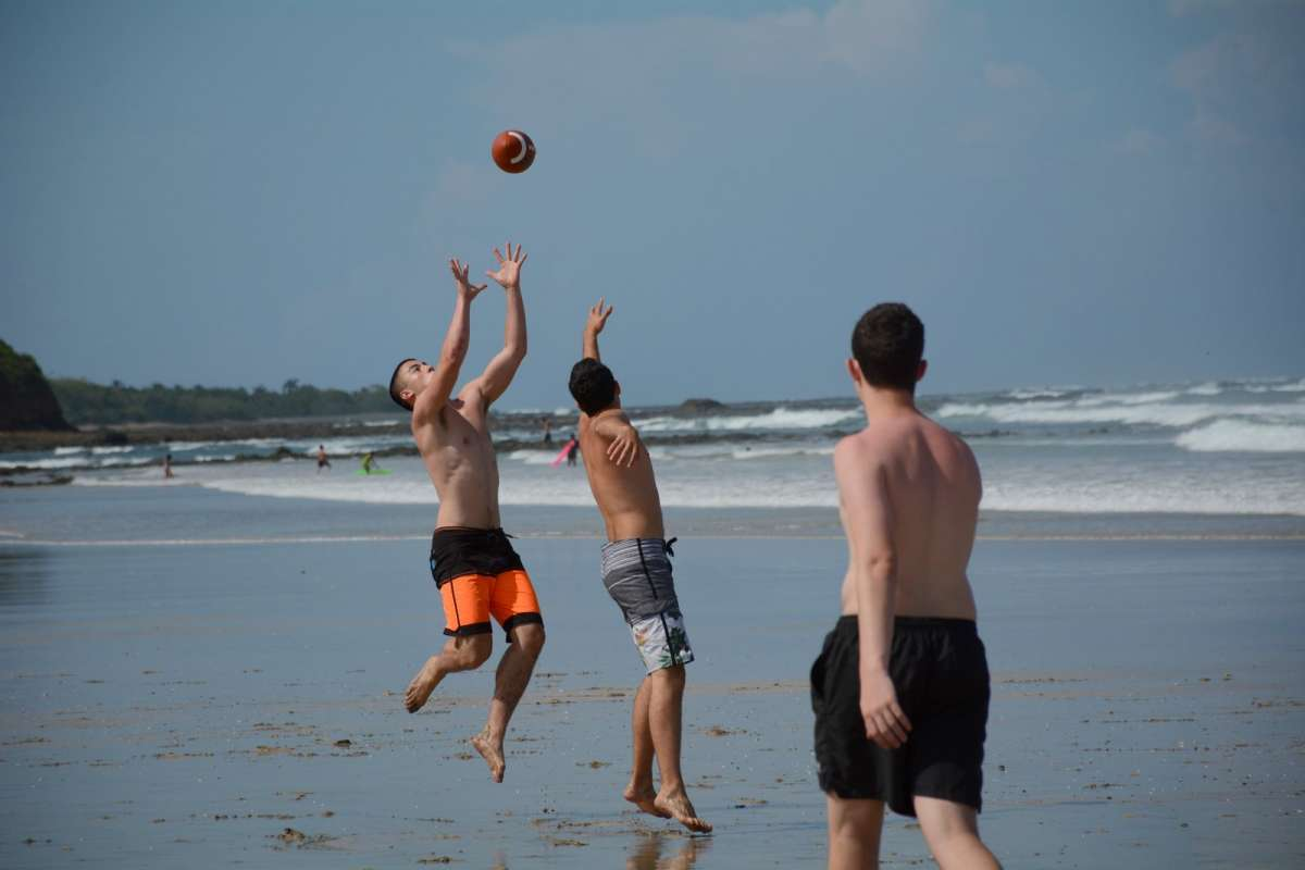 Teen boys play games on the beach on summer adventure and service program in Costa Rica.
