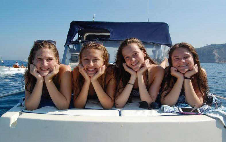 Teenage travelers go on boat cruise in Mediterranean Sea during summer youth travel program in Greece