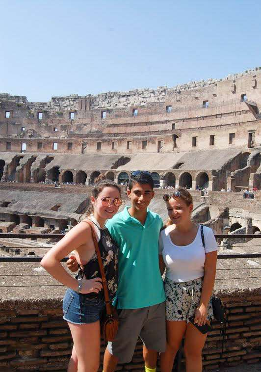 Teenage travelers explore the Colosseum in Rome during summer youth travel program in Italy
