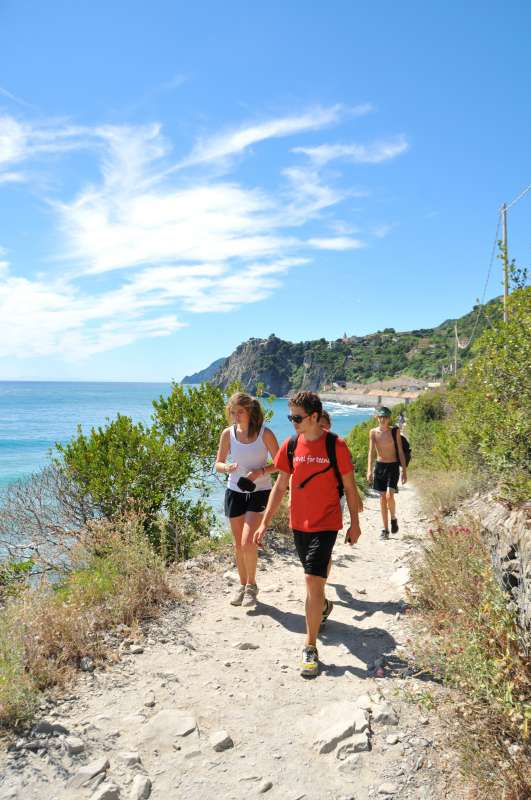 Teenage travelers hike Cinque Terre trail with views of Mediterranean on summer youth adventure program