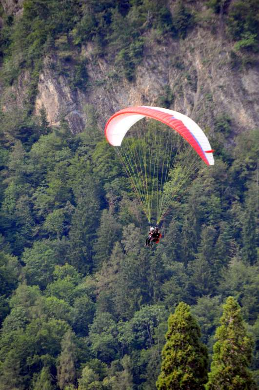 Teenage travelers paraglide in Interlaken on summer youth adventure program