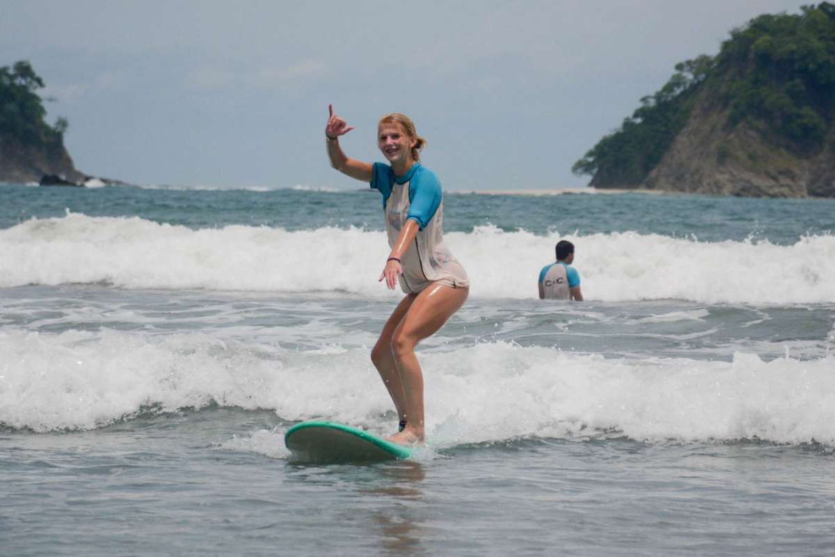A teen girl surfs in Costa Rica on her summer teen tour.