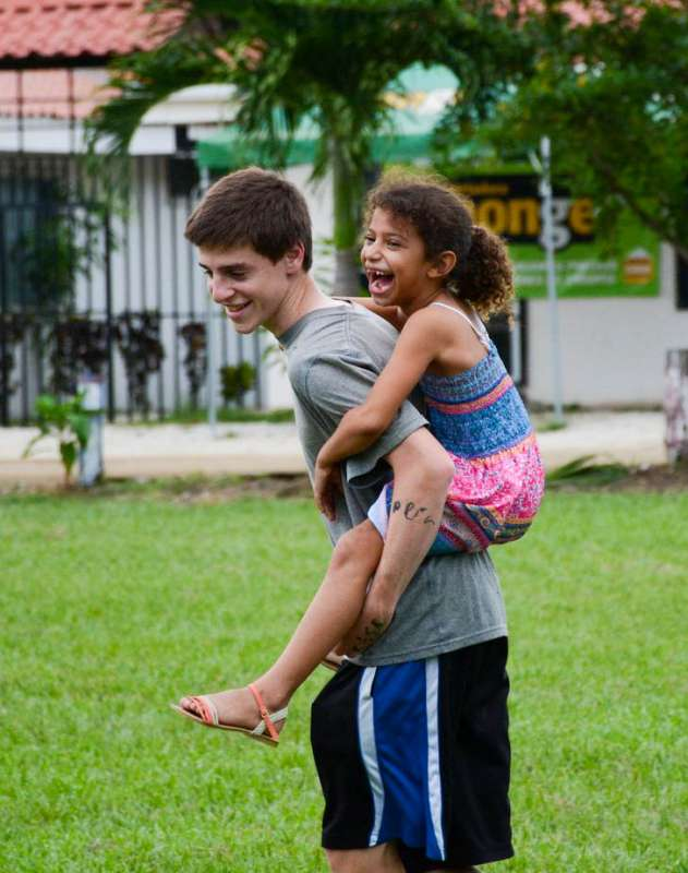 A teen plays with a local child as part of his community service teen tour in Costa Rica.