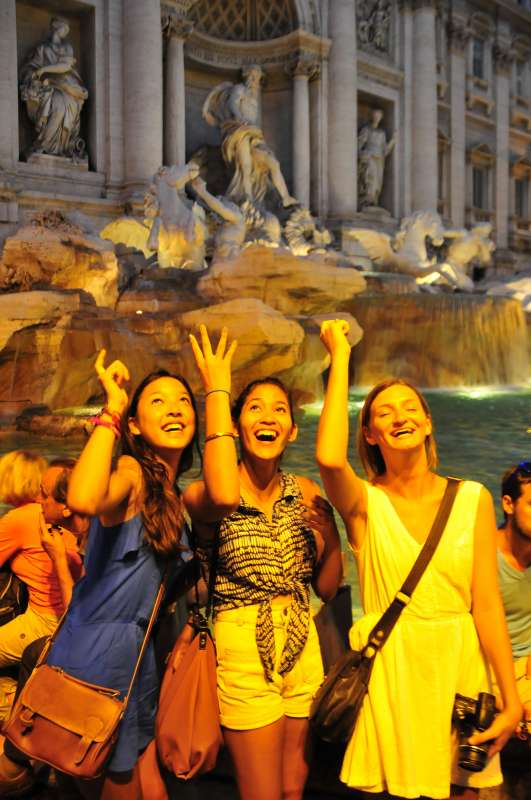 Teenage travelers toss coin in Trevi Fountain on summer teen travel program