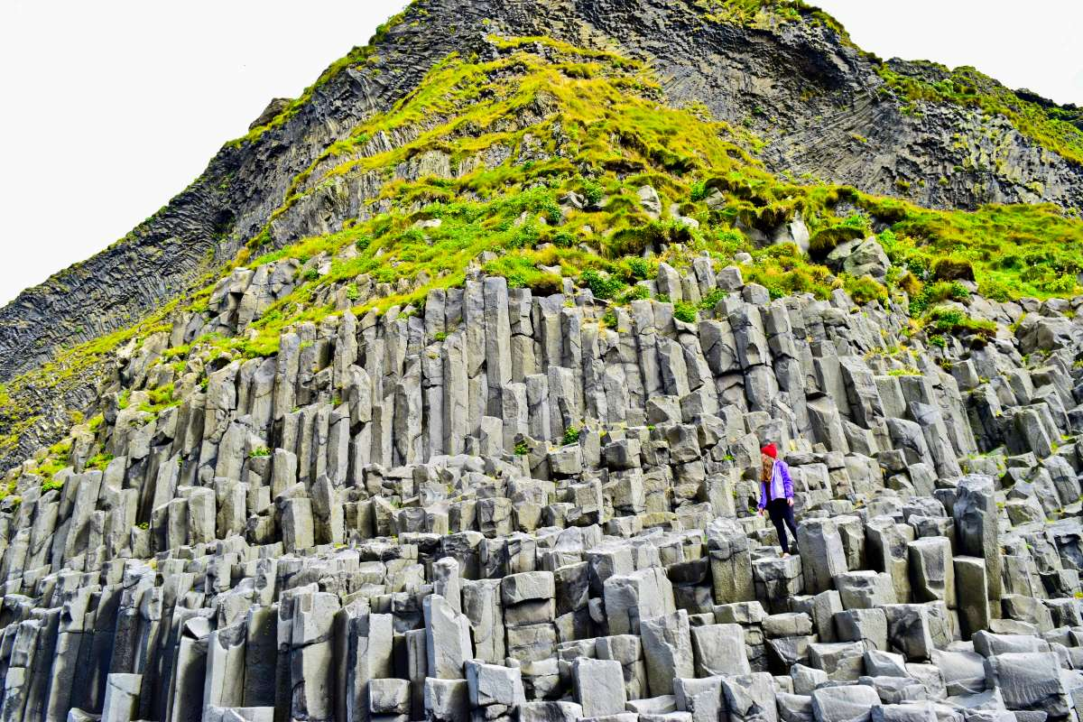 Teen with basalt rock formations in Iceland on summer adventure travel program