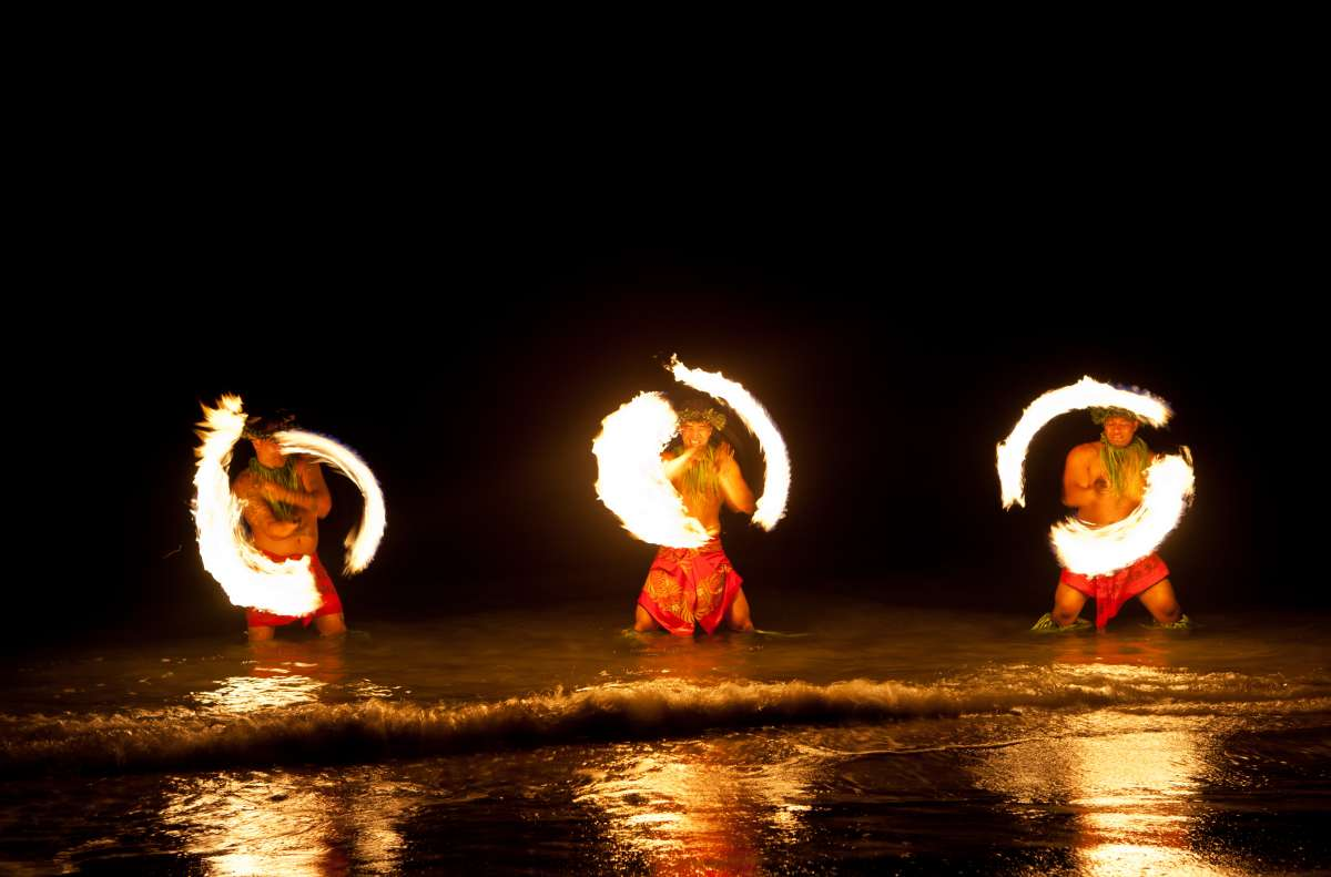 Teens enjoy a traditional fire dance in Hawaii on ultimate summer travel tour.