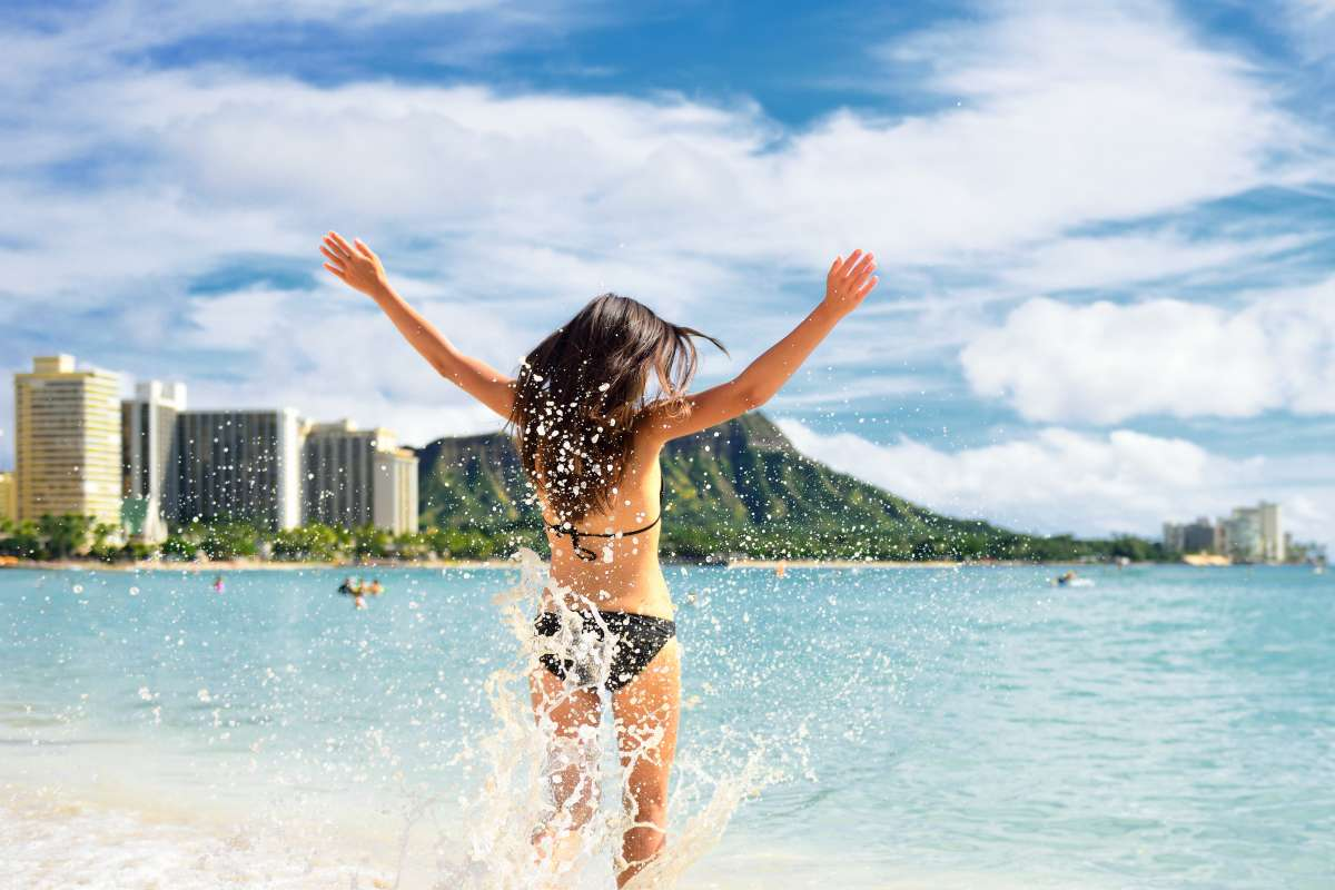 A teen splashes in the water of Hawaii on summer travel camp tour.