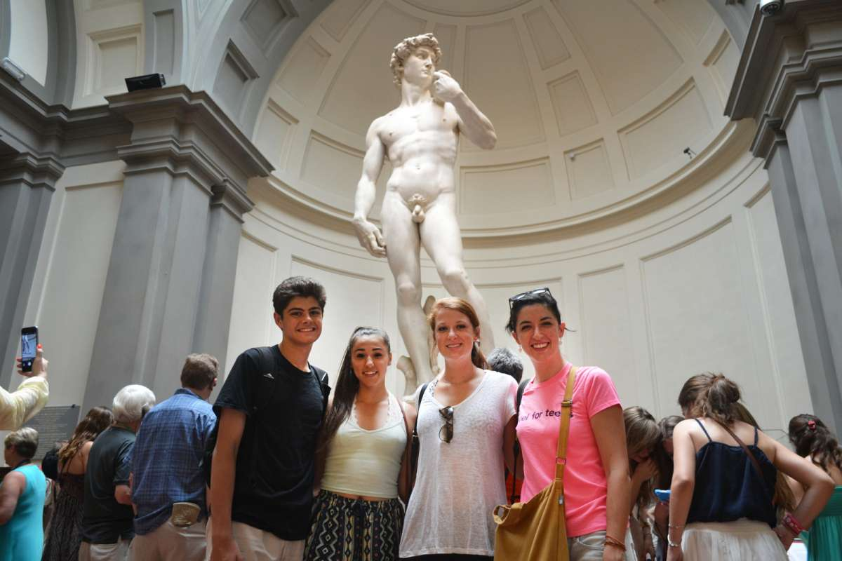 Teenage travelers see Michelangelo's David at Galleria della Accademia in Florence during summer youth travel program