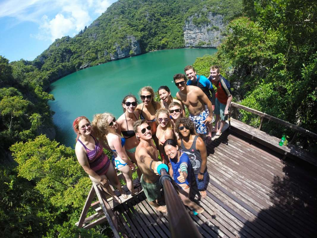 Teenage travelers pose for selfie before swimming in beautiful lake during summer youth travel program in Thailand