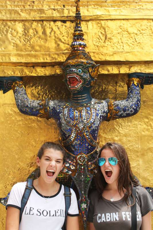 Teenage travelers have fun with statues during summer youth travel program in Thailand
