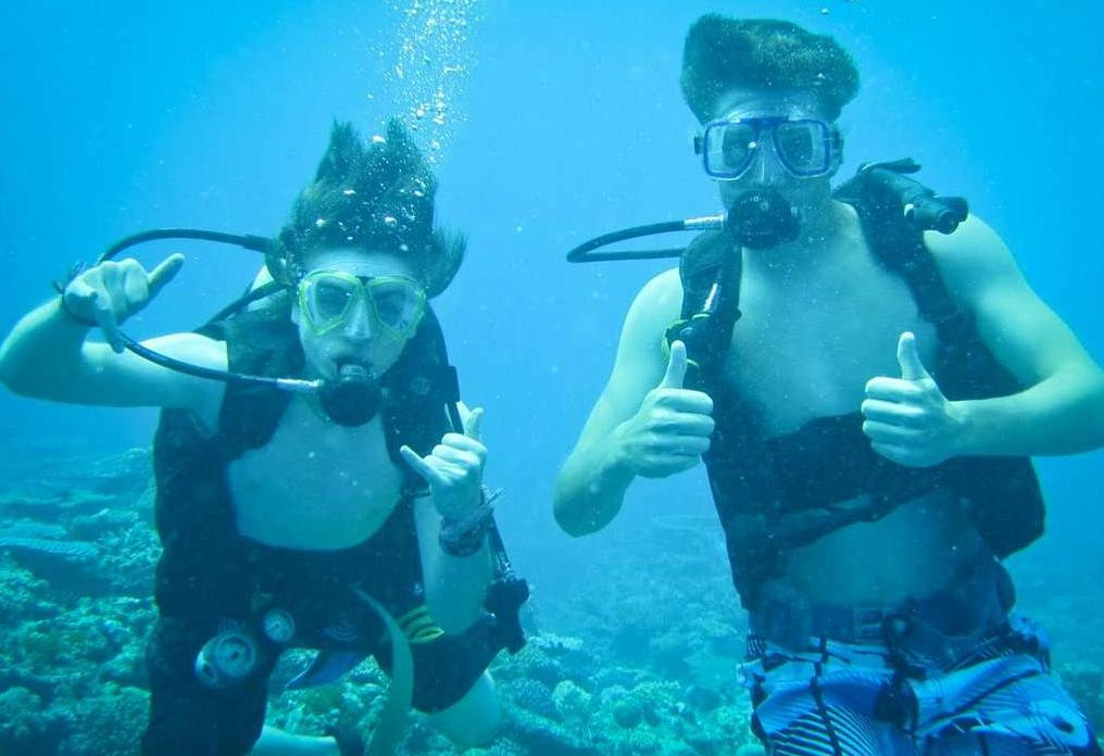 High school teens pose while scuba diving in Fiji on their summer high school program.