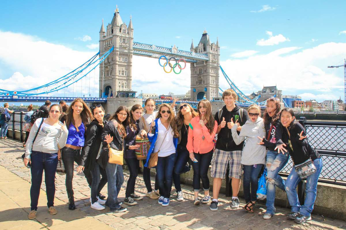 Teenage travelers with London Tower Bridge during summer youth travel program