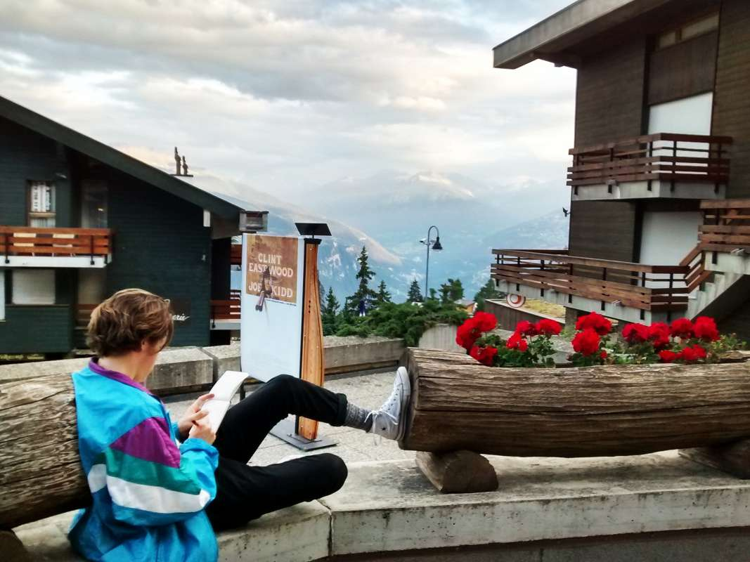 Teen relaxes in Swiss Alps during summer adventure travel program
