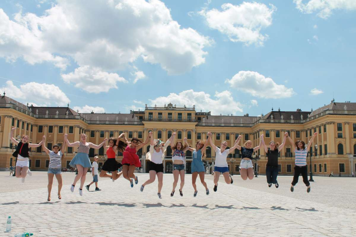 Happy teens jumping at Schonbrunn Palace Vienna on summer adventure travel program