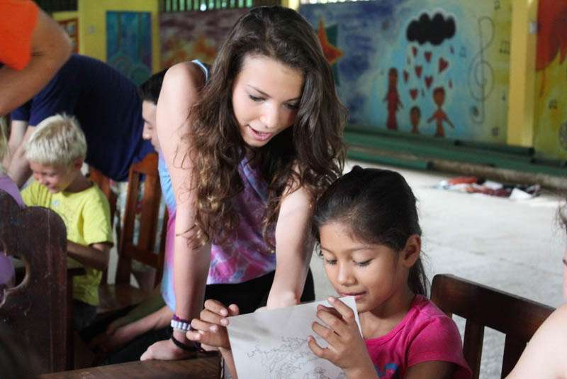 Teen works with local girl on summer service program in Costa Rica.